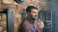 Handsome young man smoking electric e cigarette vapor indoors Stock Footage