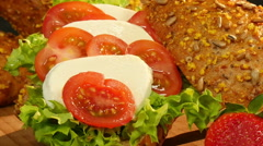 Extreme dolly zoom around spelt chia bun with tomato mozzarella Stock Footage