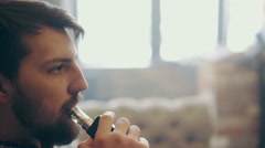 Handsome young man smoking electric e cigarette vapor indoors - stock footage
