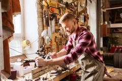 carpenter working with plane and wood at workshop - stock photo