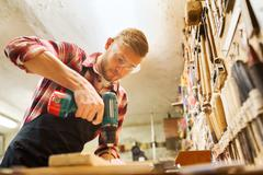 carpenter with drill drilling plank at workshop - stock photo