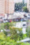 Rain drops on window and blurred cityscape Kuvituskuvat
