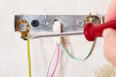 Electrician repairs wiring in wall light Stock Photos