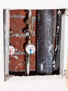 Residential water meters on pipes in niche Stock Photos