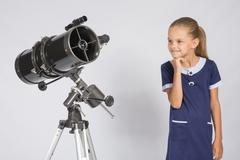 Seven-year girl with interest looking at a reflector telescope Stock Photos