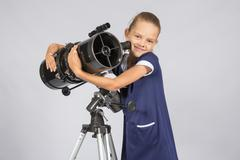 Seven-year girl hugging her given reflector telescope Stock Photos
