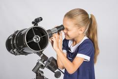 Seven-year girl squinting with interest looks in a reflector telescope Stock Photos