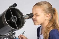 The young astronomer looks through the eyepiece of the telescope and record r - stock photo