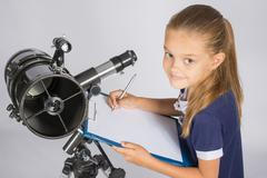 Young Astronomer writes the results of observations in the document Stock Photos