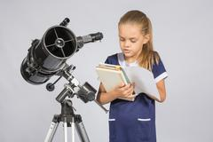 Schoolgirl reading a textbook while standing astronomer at the telescope Stock Photos