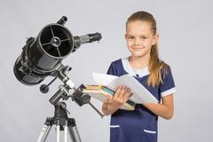 Schoolgirl astronomer leafing through books standing at the telescope Stock Photos