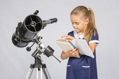 Schoolgirl astronomer leafing through books to find the right information at  Stock Photos