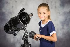 Seven-year girl adjusts the telescope and looked into the frame Stock Photos