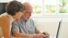 Senior couple at home using laptop computer Arkistovideo