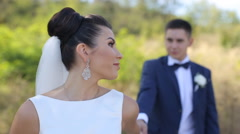 Happy beautiful bride and groom walking on field. Loving wedding couple outdoor Stock Footage