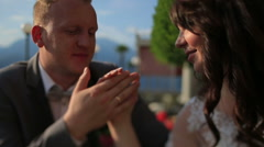 Groom softly touches bride's hand close up. Lake Como, Italy on background Stock Footage