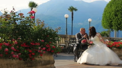 Groom kisses bride's hand in the summer cafe. Honeymoon in the Como, Italy Stock Footage