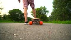 Young man starts and rides on longboard. Unrecognizable rider. Shooting from Stock Footage