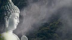 Serene artist composition of Buddha head against a cloudy rainforest - stock footage