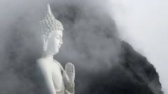 Relaxed artist composition of Buddha figure against beautiful cloudy mountains - stock footage