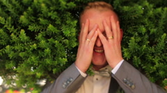 Portrait of happy groom with eyes closed on green background Stock Footage