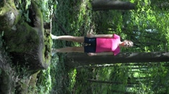 Girl in a red T-shirt and shorts do exercises in the woods. Stock Footage
