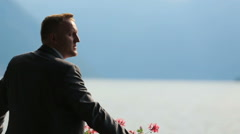 Portrait of handsome groom watching an amazing view of lake Como, Italy close up Stock Footage