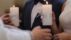Young couple in the church holds wedding candles Stock Footage