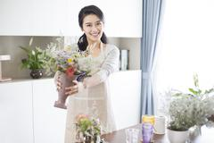 Young woman arranging flowers at home Stock Photos