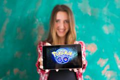 Ufa, Russia. - July 29: Woman show the tablet with Pokemon Go logo, July 29 Stock Photos