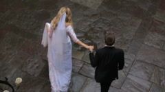 Top view of happy bride and groom at the wedding walk on wet pavement holding Stock Footage