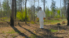 A guy in a special suit removes trash in forest Stock Footage
