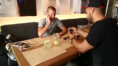 Male friends in cafe talk discuss with technology phone tablet - stock footage