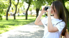 Young woman making photos with vintage film camera at summer green park. Stock Footage