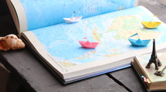 Travel to World idea or Tourism. Paper boats on the map and the Eiffel Tower Stock Footage