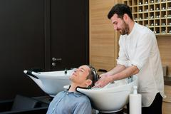 Close-up of a young man having his hair washed in hairdressing salon Stock Photos