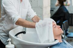 Profile view of a young man getting ready for his hair washed Stock Photos