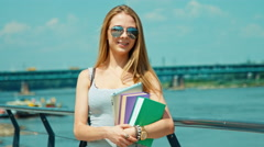 Beautiful student young woman 20-25 years smiling at camera holds her textbook Stock Footage