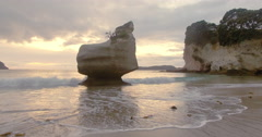 Aerial over cliff rocks at Cathedral Cove,  New Zealand Stock Footage