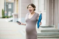 Stressed pregnant woman screaming on the street - stock photo