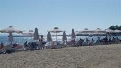 People lying on deckchairs under umbrellas on tropical sand beach,blue wavy sea. Stock Footage