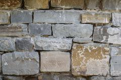 Aged stone wall with irregular block background texture Stock Photos