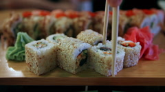 Close-up of sushi in a Japanese restaurant. Man with chopsticks taking sushi Stock Footage