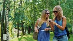 Steadicam shot: Two female friends go through the park, enjoy a smartphone Stock Footage