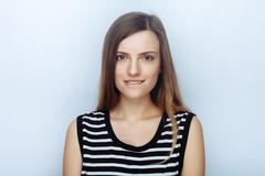 Portrait of happy young beautiful woman in striped shirt biting her lip Stock Photos