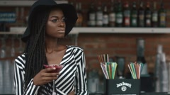 Sexy fashionable african american lady in black hat and striped vogue dress - stock footage