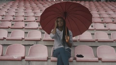 Sad african american young woman in uniform with umbrella on the stadium - stock footage