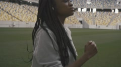 Close-up of confident african american teenage girl listening music and jogging - stock footage