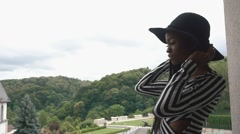 Elegant african american lady in black hat standing on the balcony of her Stock Footage