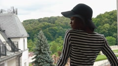 Sexy african american lady in black hat and fashionable striped dress standing - stock footage